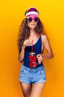 Giovane donna sensuale in abito estivo, berretto, occhiali da sole che tiene il barattolo con bevanda fresca e mentre si trova sul giallo brillante