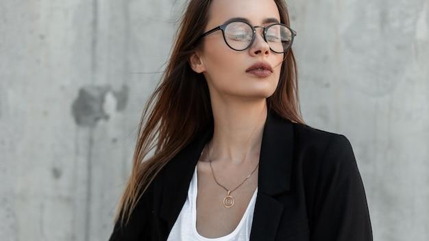 Giovane donna sensuale con belle labbra sexy in occhiali alla moda in top vintage in blazer di moda nero vicino al muro grigio godersi il fine settimana all'aperto. aspetto elegante.
