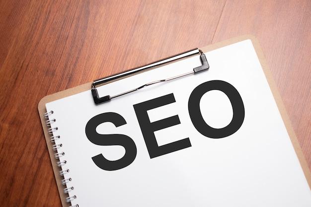Seo business, ottimizzazione dei motori di ricerca, testo seo su carta bianca sul tavolo di legno