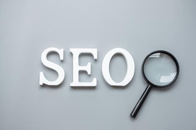 Testo seo (search engine optimization) e lente di ingrandimento su grigio. idea, visione, strategia, analisi, parole chiave e concetto di contenuto