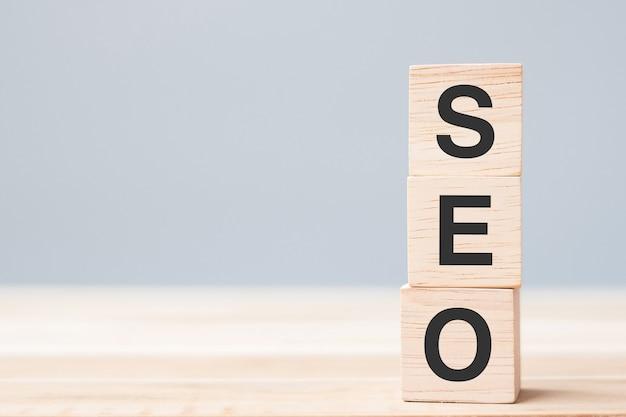 Seo (search engine optimization) testo blocchi cubo di legno sullo sfondo della tabella. idea, strategia, marketing, parole chiave e concetto di contenuto