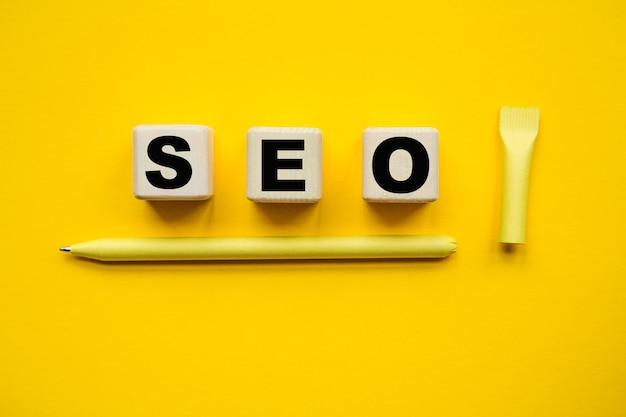 Seo - su cubi gialli e una carta, penna gialla su sfondo giallo. una soluzione brillante per il concetto di business, finanziario, marketing
