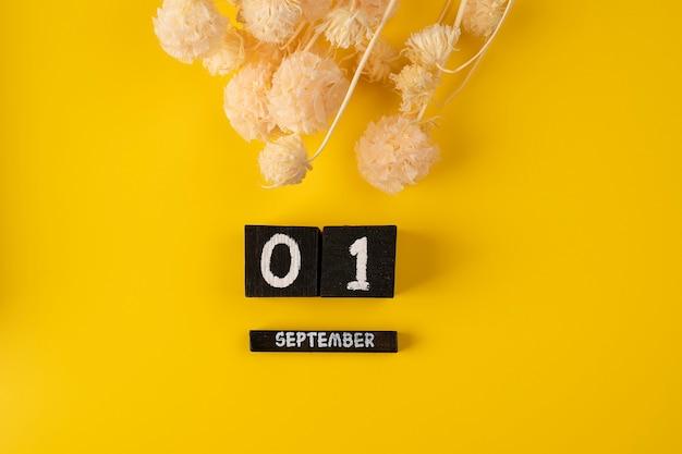 Cubo del calendario in legno del 1 settembre su sfondo giallo per lo sfondo della data di ritorno a scuola piatta
