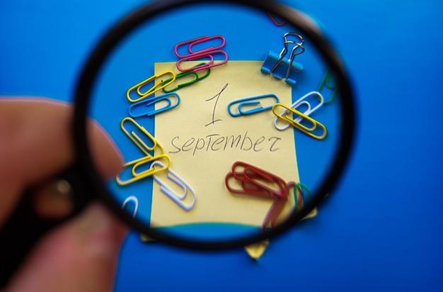 Concetto del primo giorno di settembre. 1 settembre, calendario con lente d'ingrandimento su sfondo blu e graffette.