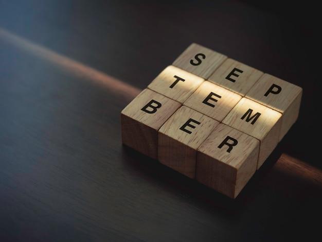 Settembre, parole su blocchi di cubo di legno su fondo di legno marrone scuro con spazio di copia.