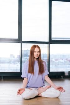Serena attraente giovane donna meditando seduta sul pavimento nella posa del loto sullo sfondo della finestra nella stanza dell'ufficio luminoso.