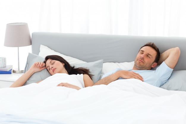 Serene coppia che dorme sul loro letto al mattino