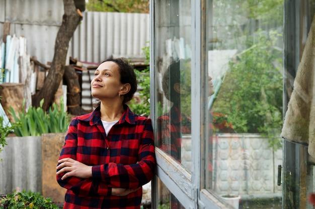 Giardiniere serena della donna matura che posa alla macchina fotografica che distoglie lo sguardo mentre si appoggia su una finestra di una vecchia serra del paese. hobby, legno, natura, concetto di giardinaggio