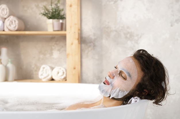 Giovane sereno e rilassato con maschera facciale che gode del bagno caldo con schiuma mentre trascorre il tempo in bagno