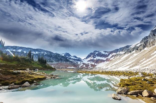 Serena scena in riva al lago di montagna con il riflesso delle rocce nell'acqua calma.