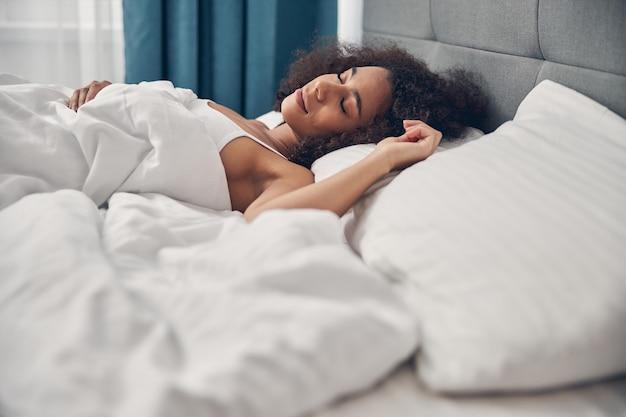 Serena giovane donna con i capelli ricci che dorme pacificamente nel suo letto a casa
