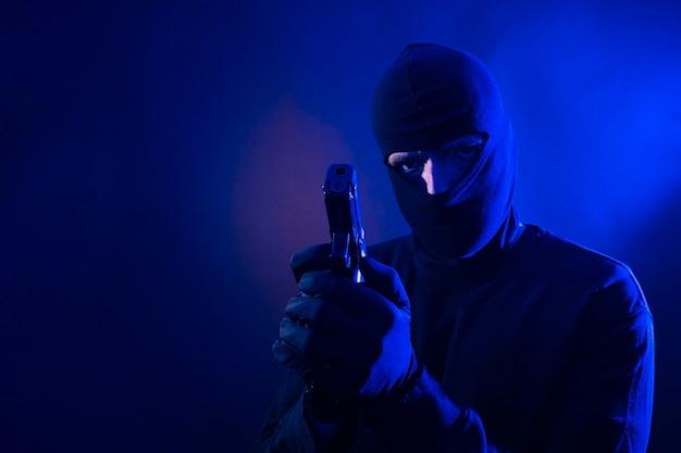 Serie di un ladro caucasico che irrompe in una casa con la pistola in mano. include le luci della polizia.
