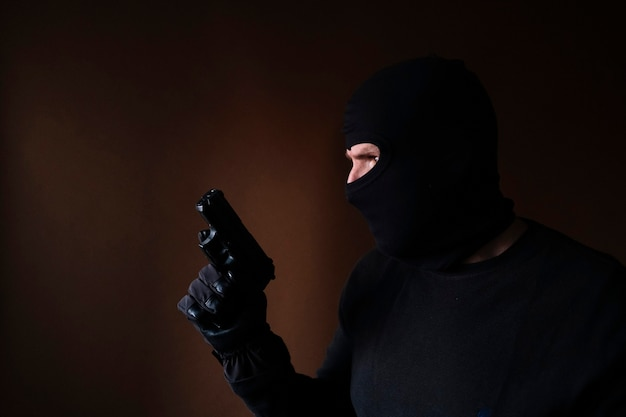 Serie di un ladro caucasico che irrompe in una casa con la pistola in mano.