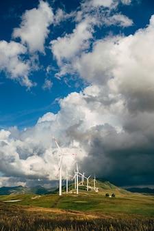 Una serie di generatori eolici tra nuvole epiche