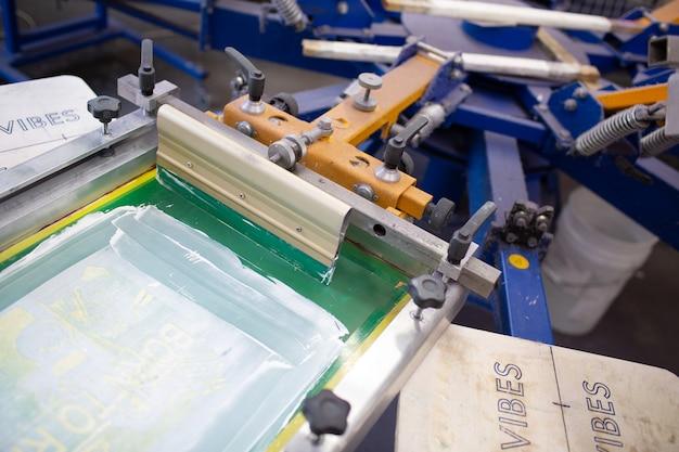 Processo di stampa serigrafica serigrafica presso la fabbrica di abbigliamento. carosello telaio, tergipavimento e colori plastisol.