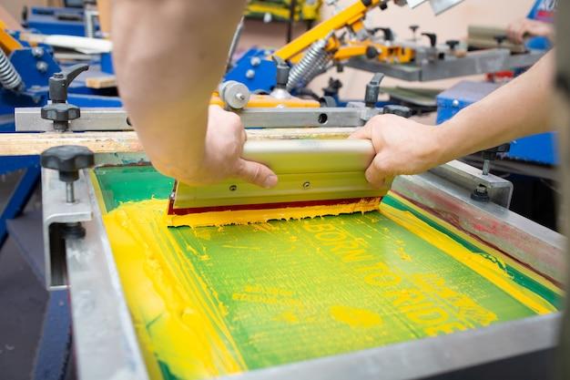 Processo di stampa serigrafica serigrafica presso la fabbrica di abbigliamento. vernici colorate per telaio, tergipavimento e plastisol