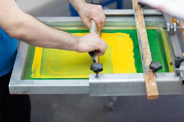 Processo di stampa serigrafica serigrafica presso la fabbrica di vestiti racla telaio e vernici colorate plastisol