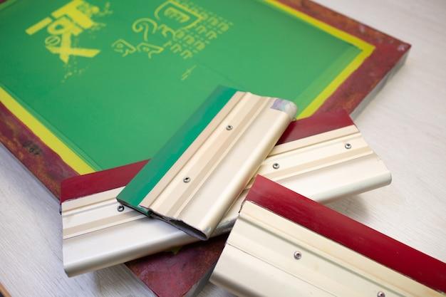 Processo di stampa serigrafica serigrafica presso la fabbrica di abbigliamento. stencil cornice e tergipavimento.