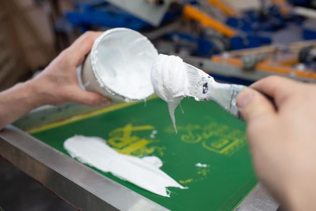 Processo di stampa serigrafica serigrafica presso la fabbrica di abbigliamento. applicazione di vernice su telaio, tergipavimento e vernici colorate plastisol