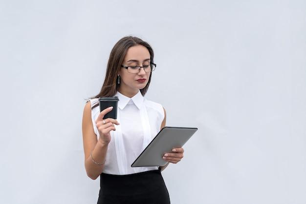Serios donna d'affari con una tazza di caffè e un computer tablet isolato su sfondo grigio bianco