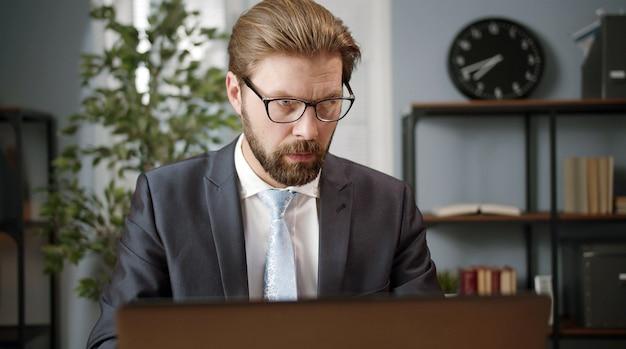 Uomo d'affari adulto serio in occhiali e abbigliamento formale che si siede alla scrivania e che lavora al computer portatile