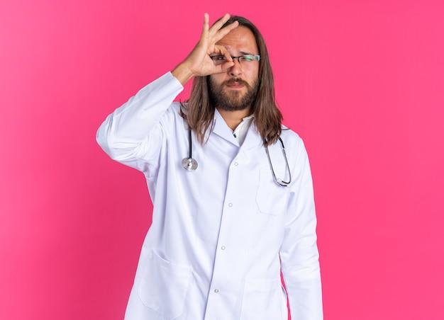 Medico maschio adulto serio che indossa accappatoio medico e stetoscopio con gli occhiali che strizzano l'occhio facendo un gesto di sguardo guardando la telecamera isolata sulla parete rosa