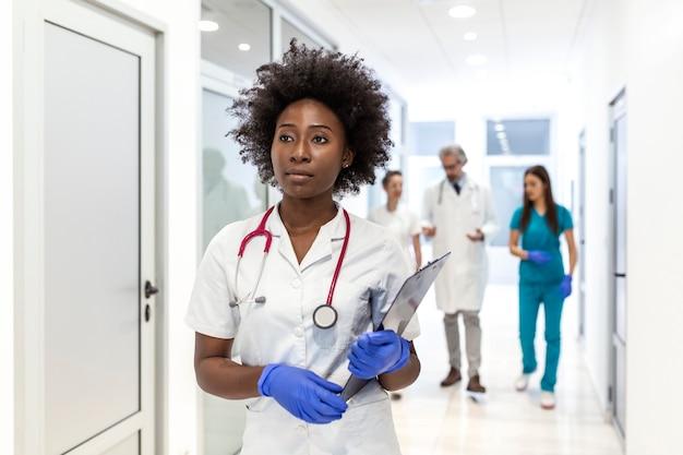 Medico femminile afroamericano serio che cammina con i risultati dei test dei pazienti prima dell'incontro con il paziente.