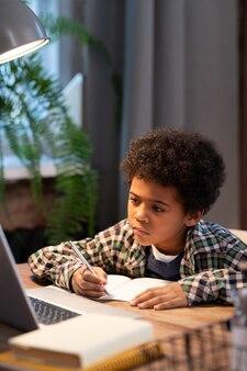 Scolaro africano serio che prende appunti in quaderno mentre è seduto al tavolo davanti al laptop e guarda il display durante la lezione online