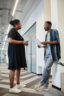 Imprenditori afroamericani seri che confrontano i dati nei loro rapporti quando si incontrano nel corridoio di mo...