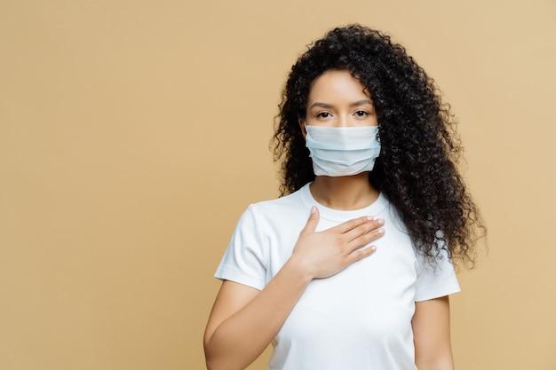 Una donna afroamericana seria indossa una maschera medica, ha problemi di respirazione, preme la mano contro il petto, si è infettata con il coronavirus