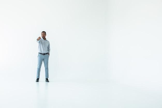 Uomo serio afro americano in piedi contro il muro bianco e indicandoti