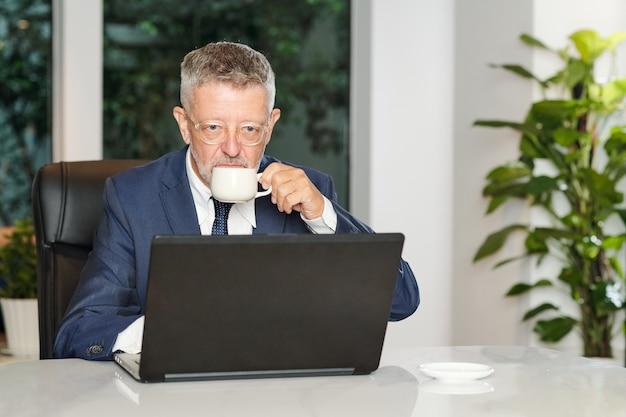 Uomo d'affari invecchiato serio che beve caffè espresso del mattino e legge le notizie sullo schermo del laptop nella caffetteria