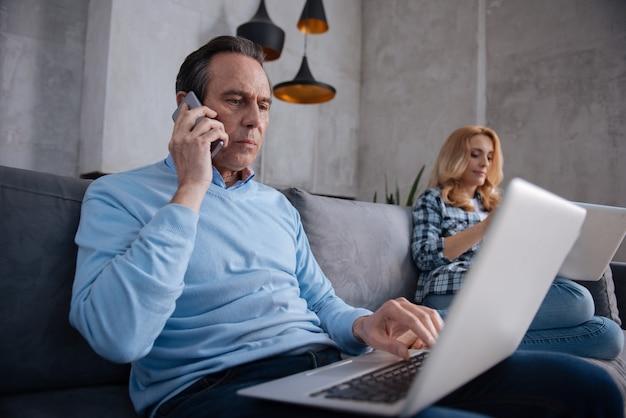 L'invecchiamento grave ha coinvolto l'uomo seduto a casa e l'utilizzo di gadget moderni con la moglie mentre navigava in internet e conversava di lavoro