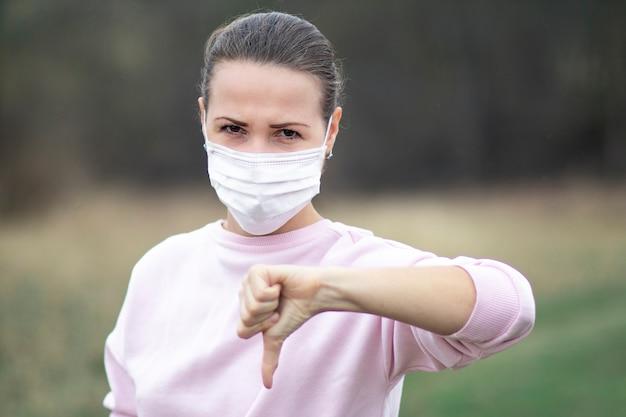 La ragazza arrabbiata seria, la giovane donna nella mascherina medica sterile protettiva sul suo fronte all'aperto mostra il pollice giù, l'antipatia. virus, coronavirus pandemico, concetto. covid-19