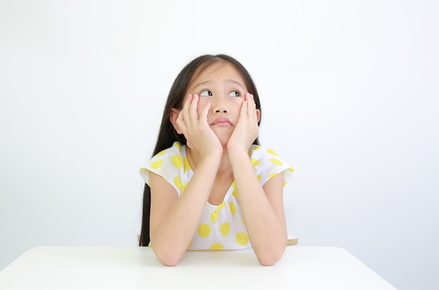 Seria bambina asiatica che riposa il mento sulle mani con lo sguardo sul tavolo su sfondo bianco