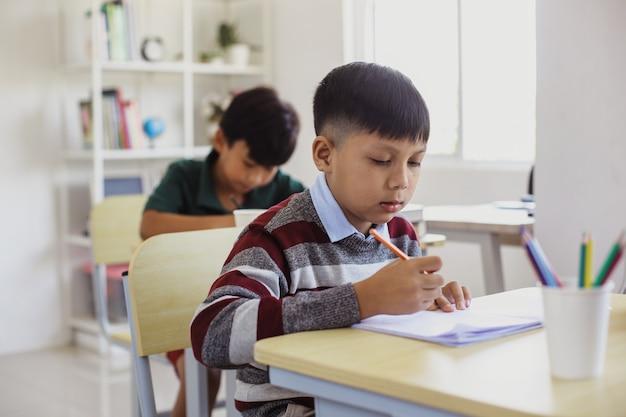 Gli studenti asiatici seri studiano e scrivono durante la lezione in classe