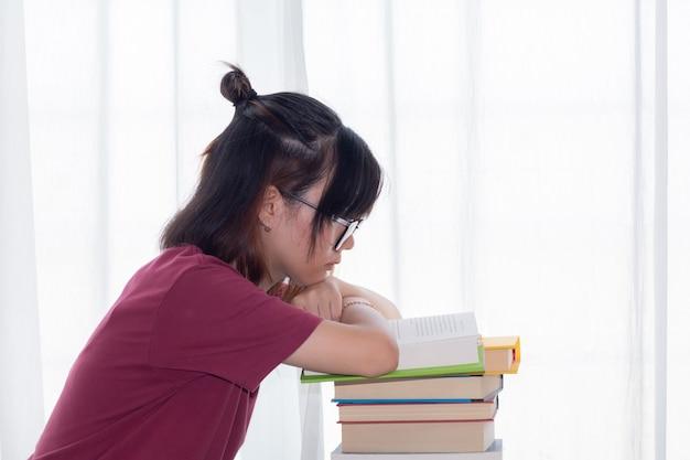 La ragazza teenager asiatica seria con gli occhiali presta il libro di lettura dell'attenzione per l'esame o la concorrenza