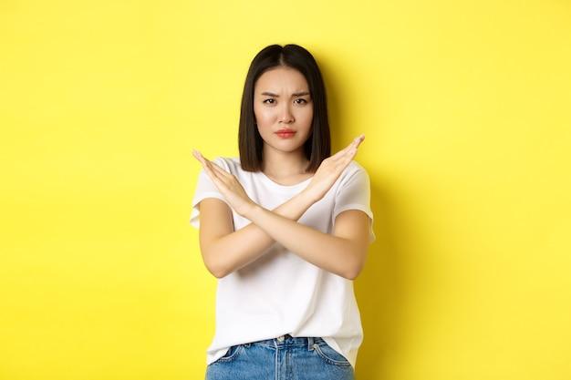 Donna coreana seria e assertiva che mostra il gesto di arresto trasversale, aggrottando la fronte e dicendo di no, proibire l'azione, disapprovare qualcosa di brutto, in piedi su sfondo giallo.