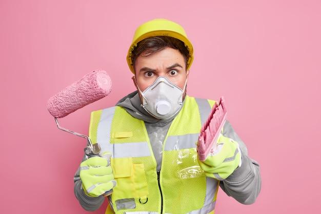 L'ingegnere serio e attento indossa la maschera protettiva del casco e l'uniforme di sicurezza tiene l'attrezzatura da costruzione impegnata nella ricostruzione dell'appartamento