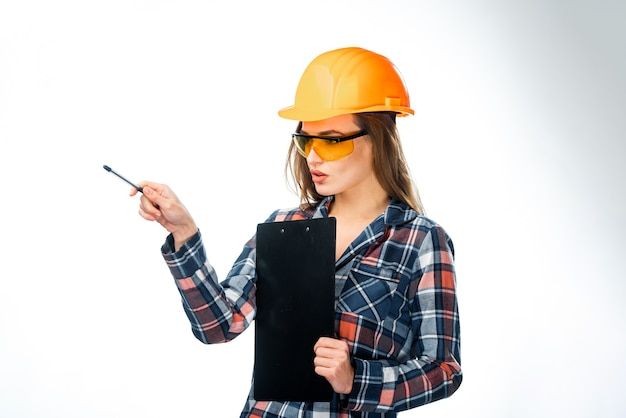 Donna attraente seria dell'architetto con il casco. isolato su sfondo bianco. intelligente, intelligente, bella elegante bella ragazza bruna carina in abiti casual. indossare occhiali protettivi, tenere cartella.