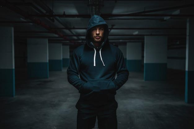 Sportivo caucasico muscolare attraente serio in felpa con cappuccio in piedi nel garage sotterraneo con le mani in tasca durante la notte. concetto di vita urbana.