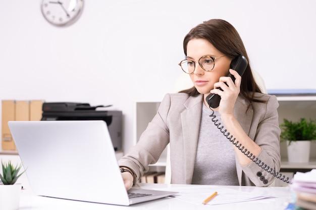 Giovane segretaria attraente seria in vetri che risponde alla telefonata durante la ricerca di informazioni sul computer portatile in ufficio
