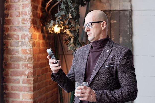 Grave uomo calvo in dolcevita e giacca in piedi nella hall e controllare il messaggio sul telefono