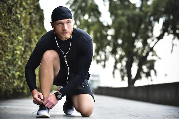 Giovane sportivo caucasico barbuto serio che lega i lacci delle scarpe sulle sue scarpe da ginnastica al parco cittadino.