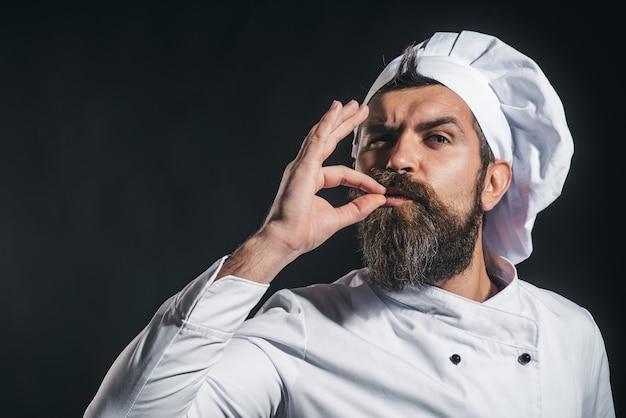 Cuoco o fornaio serio barbuto che gesturing eccellente chef maschio in uniforme bianca con segno perfetto