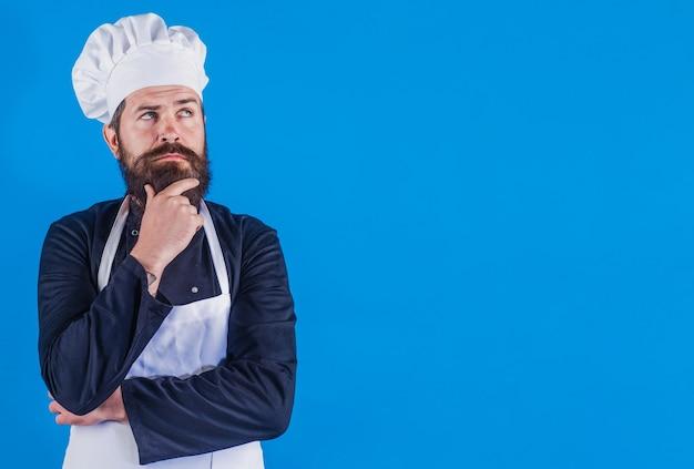 Chef barbuto serio in uniforme. cuoco professionista. cucina del ristorante. cucinando. pubblicità.