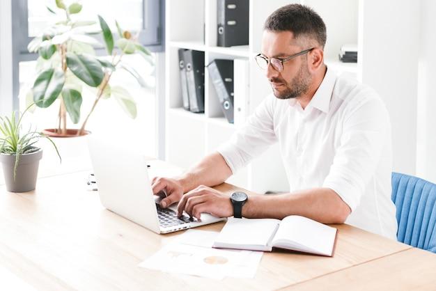 Uomo barbuto serio anni '30 in camicia bianca seduto al tavolo e digitando sul computer portatile, mentre si lavora nella luminosa sala ufficio