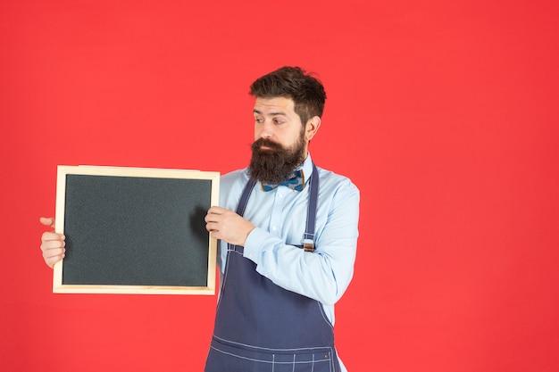 L'uomo barbuto serio in grembiule da barbiere tiene lo spazio rosso della copia del fondo rosso del bordo di pubblicità del barbiere, scuola.