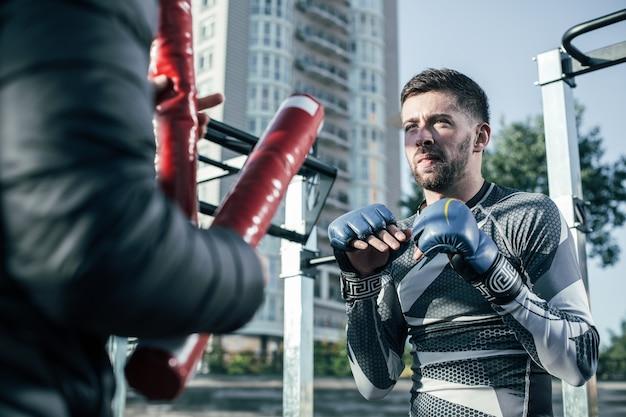 Pugile mma barbuto serio in piedi di fronte al suo allenatore e fiducioso mentre guarda i bastoni da boxe nelle sue mani