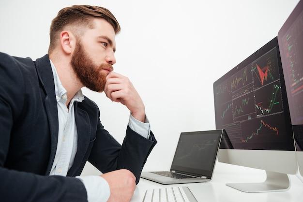 Giovane uomo d'affari barbuto serio che si siede e lavora con il computer in ufficio